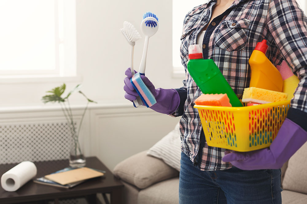 Unrecognizable woman with cleaning equipment ready to clean house. Professional cleaning service concept, copy space